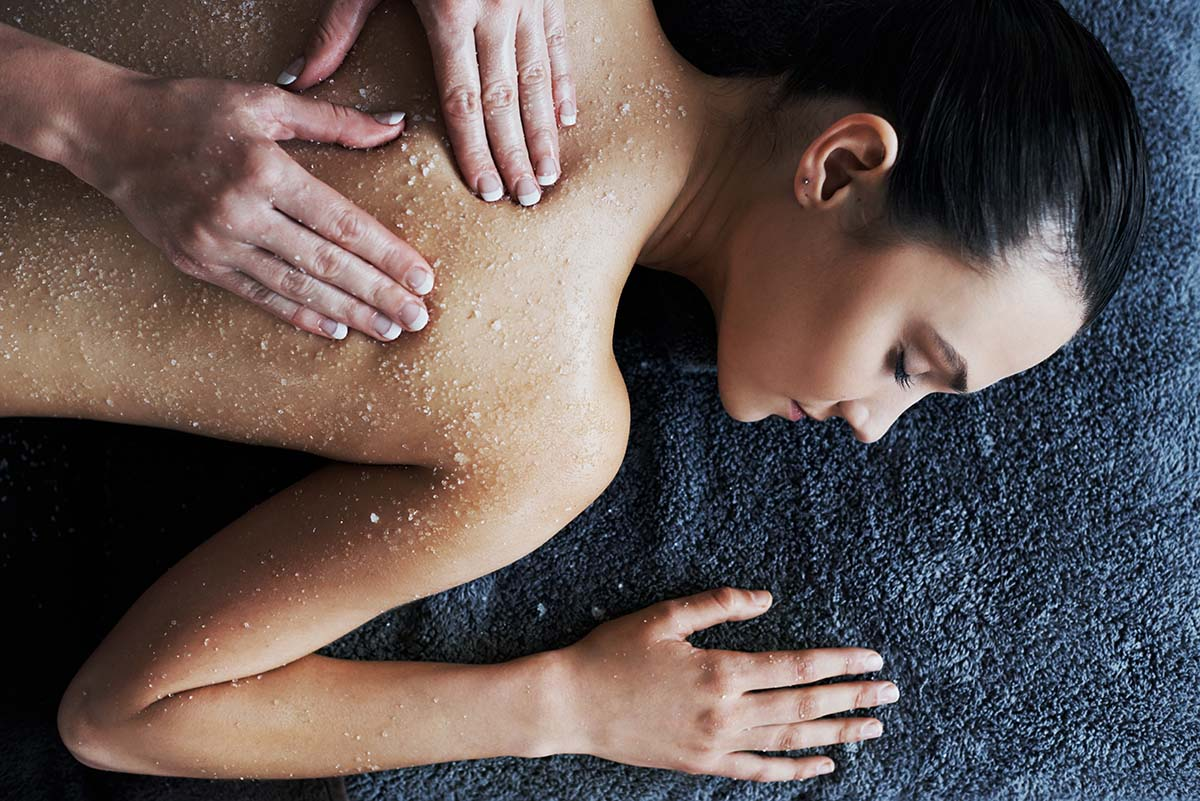 Shot of a young woman getting a back scrub at a spa